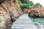 Old vintage wooden walking bridge over sea water