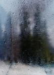 Rainy autumn landscape through a window with raindrops. autumnal mood.
