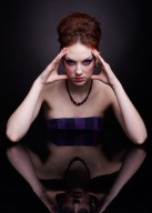 portrait of beautiful young woman sitting at dark reflecting table touching head temples with hands