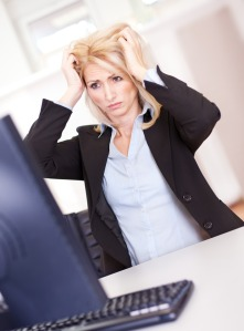 Stressful business woman working on computer at the office