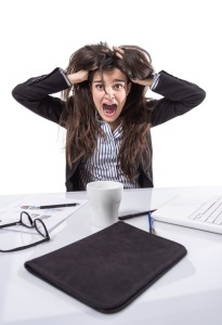 Portrait of crazy stressed young business woman screaming and pulling her hair over white background
